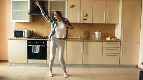 Vrolijke jonge grappige vrouw die en met gietlepel thuis dansen zingen terwijl het hebben van vrije tijd in de keuken royalty-vrije stock fotografie
