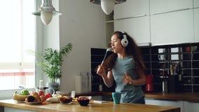 Vrolijke jonge grappige vrouw die en met gietlepel thuis dansen zingen terwijl het hebben van vrije tijd in de keuken stock videobeelden