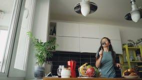 Vrolijke jonge grappige vrouw die en met gietlepel thuis dansen zingen terwijl het hebben van vrije tijd in de keuken stock footage