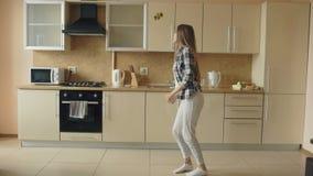Vrolijke jonge grappige vrouw die en met gietlepel thuis dansen zingen terwijl het hebben van vrije tijd in de keuken stock video