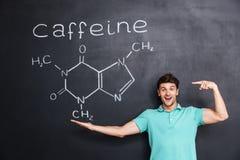 Vrolijke jonge leraar die op chemische structuur van cafeïnemolecule richten Stock Foto