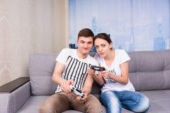 Vrolijke jonge mannelijke en vrouwelijke gamers die videospelletje spelen stock foto's