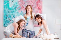 Vrolijke jonge meisje het vechten hoofdkussens op het bed thuis Stock Afbeelding