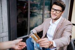 Vrolijke jonge mens die door creditcard in openluchtkoffie betalen Royalty-vrije Stock Foto