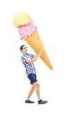 Vrolijke jonge mens die een enorm roomijs dragen stock afbeelding