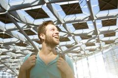 Vrolijke jonge mens die met zak in luchthaven glimlachen Stock Foto