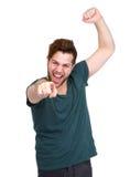 Vrolijke jonge mens die vinger richten Stock Afbeelding