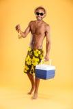 Vrolijke jonge mens in hoed en zonnebril die koelere zak houden Stock Afbeelding