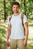 Vrolijke jonge mens met rugzak die zich in bos bevinden royalty-vrije stock foto's