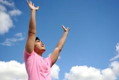 Vrolijke jonge mens tegen blauwe hemel Royalty-vrije Stock Foto's