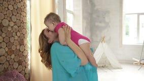 Vrolijke jonge moeder die haar babymeisje opheffen stock video