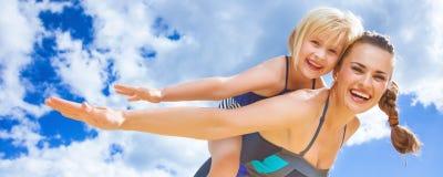 Vrolijke jonge moeder en dochter op strand dat prettijd heeft royalty-vrije stock afbeelding