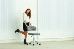 Vrolijke jonge onderneemster die zich dichtbij de stoel bevindt Royalty-vrije Stock Fotografie