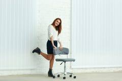 Vrolijke jonge onderneemster die zich dichtbij de stoel bevinden Stock Afbeelding