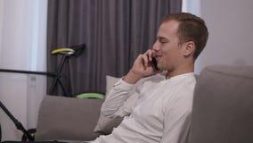 Vrolijke jonge op de mobiele telefoon spreken en zakenman die terwijl het zitten op bank in moderne ruimte met zolder glimlachen stock footage