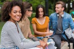Vrolijke jonge studenten die in park spreken Stock Afbeeldingen