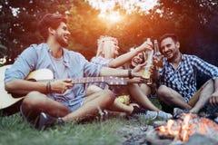 Vrolijke jonge vrienden die pret hebben door kampvuur Royalty-vrije Stock Foto's