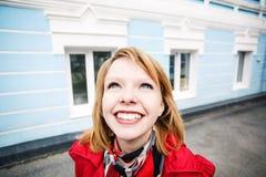Vrolijke jonge vrouw die in de straat glimlachen Royalty-vrije Stock Foto's