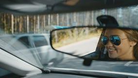 Vrolijke jonge vrouw die door auto reizen stock videobeelden