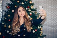 Vrolijke jonge vrouw die Kerstmis selfie met smartphone nemen stock afbeelding