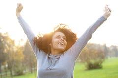 Vrolijke jonge vrouw die met opgeheven wapens glimlachen Stock Foto