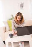 Vrolijke jonge vrouw die thuis met laptop werken Stock Foto