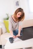 Vrolijke jonge vrouw die thuis met laptop werken Stock Foto's