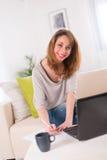 Vrolijke jonge vrouw die thuis met laptop werken Royalty-vrije Stock Foto