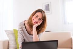 Vrolijke jonge vrouw die thuis met laptop werken Royalty-vrije Stock Afbeelding