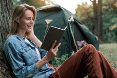 Vrolijke jonge vrouw die van literatuur in bos genieten stock afbeelding