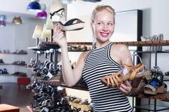 Vrolijke jonge vrouw die van twee paren schoenen kijken Royalty-vrije Stock Foto's