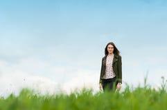Vrolijke jonge vrouw die zich buiten op groene weide bevinden stock foto's