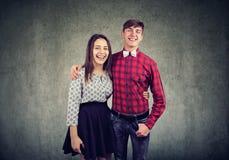 Vrolijke jonge vrouw en man die, en bij camera bekijken glimlachen elkaar omhelzen royalty-vrije stock afbeeldingen
