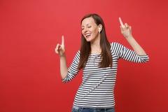 Vrolijke jonge vrouw met draadloze oortelefoons die, benadrukkend wijsvingers, het luisteren muziek dansen die op helder rood wor stock foto