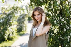 Vrolijke jonge vrouw met een mooie glimlach met natuurlijke samenstelling met blauwe ogen in een elegant de zomer beige vest royalty-vrije stock foto