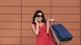 Vrolijke jonge vrouw met het winkelen zakken die op de telefoon spreken stock video