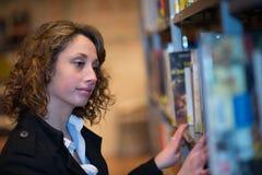Vrolijke jonge vrouw in openbare bibliotheek Stock Foto's