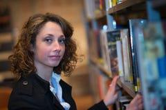 Vrolijke jonge vrouw in openbare bibliotheek Stock Afbeeldingen
