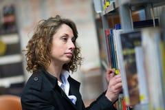 Vrolijke jonge vrouw in openbare bibliotheek Royalty-vrije Stock Afbeeldingen