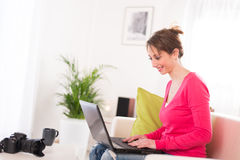 Vrolijke jonge vrouw thuis met laptop computer Royalty-vrije Stock Foto's