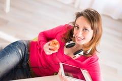 Vrolijke jonge vrouw thuis met tablet compuer Stock Foto's