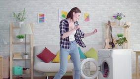 Vrolijke jonge vrouwen housewifewashes kleren en dansen in moderne flat stock video