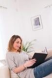 Vrolijke jonge vrouwenlezing thuis Royalty-vrije Stock Foto's