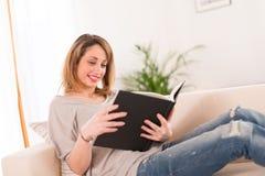 Vrolijke jonge vrouwenlezing thuis Stock Foto's