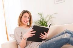 Vrolijke jonge vrouwenlezing thuis Stock Foto