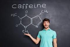 Vrolijke jonge wetenschapper die chemische structuur van cafeïnemolecule tonen Royalty-vrije Stock Foto's
