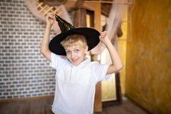 Vrolijke jongen die nieuwe tovenaarshoed dragen stock afbeeldingen