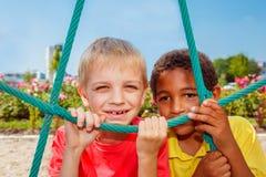 Vrolijke jongens bij de speelplaats Stock Foto