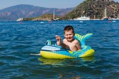 Vrolijke jongenszitting in een opblaasbare boot op het overzees stock foto