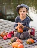 Vrolijke jongenszitting met Halloween-pompoenen Stock Fotografie